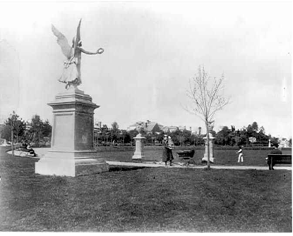 View of Prahran Public Gardens, showing a female statue called 'Winged Victory', and two concrete urns. The statuary and a fountain were donated by Cr. George William Taylor, as a gift to the citizens in 1888. The original statue of the female and the urns were removed and replaced with re-cast pieces around 1989. The original deteriorated statuary was placed in the courtyard at the Prahran Town Hall.